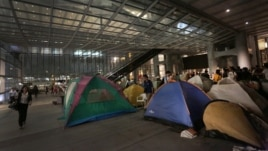 People walk past protesters' tents outside the HSBC headquarters in Hong Kong, August. 27, 2012.