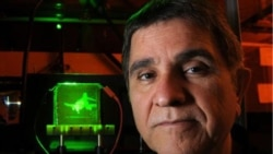University of Arizona scientist Nasser Peyghambarian stands in front of his holographic display