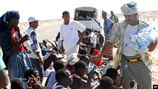 A Yemeni NGO worker distributes water on Somali asylum seekers upon their arrival on the beach of Hasn Beleid village, 230 kms east of the Red Sea port of Aden, (File October 15, 2008).