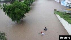 지난 19일 멕시코 쿨리아칸 시에서 사람들이 홍수 속을 헤엄치고 있다.