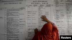 A woman leans against a ferry passenger list as she searches for information about family members who were on board a sunken ferry, at a rescue command post in Siwa, Wajo, South Sulawesi, Indonesia, Dec. 21, 2015.