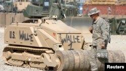 """Một binh sĩ Mỹ đi ngang qua con robot dọn mìn được đặt theo tên một nhân vật họat hình """"Wall-E"""" tại trại Leatherneck ở tỉnh Helmand, miền nam Afghanistan, 10/3/2010. REUTERS/Shamil Zhumatov"""