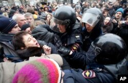FILE - Russian police officers detain opposition activists outside a court room in Moscow, Russia, Monday, Feb. 24, 2014, where hearings started against opposition activists detained on May 6, 2012 during a rally at Bolotnaya Square.