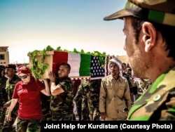 FILE - People carry the coffin of American volunteer Leland Scott during burial ceremony in Sharfadin shrine, Duhok, Iraq, June 21, 2016.