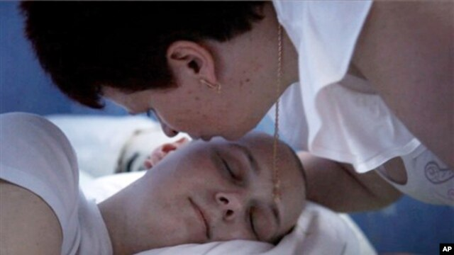 In this undated photo made available by Scott Anger & Bob Sacha for the Open Society Foundations, in Cherkasy, Ukraine, Nadezhda Zhukovsky, 50, kisses her sleeping son Vlad, who died of brain cancer last year at age 27, before going to the local pharmacy
