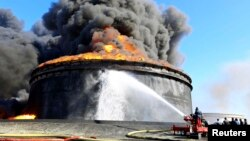 Firefighters trained hoses on a flaming oil storage tank in Es Sider a month ago. The fire began when militias in attack vessels fired rockets at the storage facility.