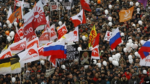 Demonstrators hold Russian opposition flags during a rally protesting against election fraud in Moscow, Saturday, Dec. 24, 2011.