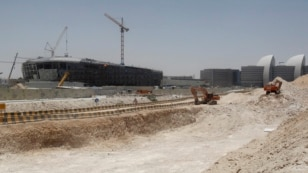 FILE - Construction cranes and bulldozers operate in Doha, June 25, 2013.