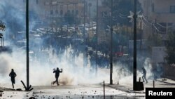 Waandamanaji wa Palestina wakikimbia mabomu ya machozi yanayotupwa na polisi wa Israel.