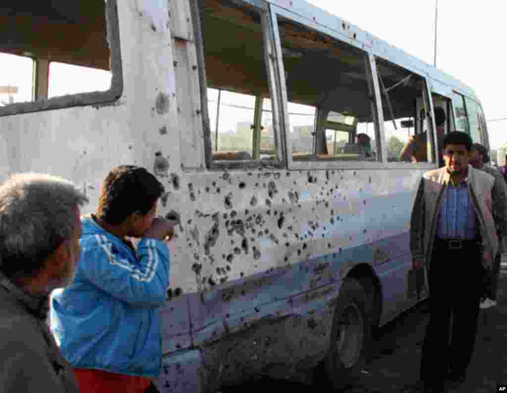People inspect a damaged bus after a bomb attack in Sadr city in eastern Baghdad on January 5, 2012. (Reuters)