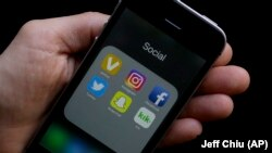 FILE: Some social media apps on a smartphone help by an Associated Press reporter in San Francisco, CA.