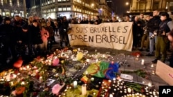 "People hold a banner reading ""I am Brussels"" behind flowers and candles to mourn for the victims at Place de la Bourse in the center of Brussels, March 22, 2016."