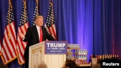 Republican U.S. presidential candidate Donald Trump speaks in front of a display of Trump water, wine and steaks as he talks about the results of the Michigan, Mississippi and other primary elections during a news conference held at his Trump National Gol