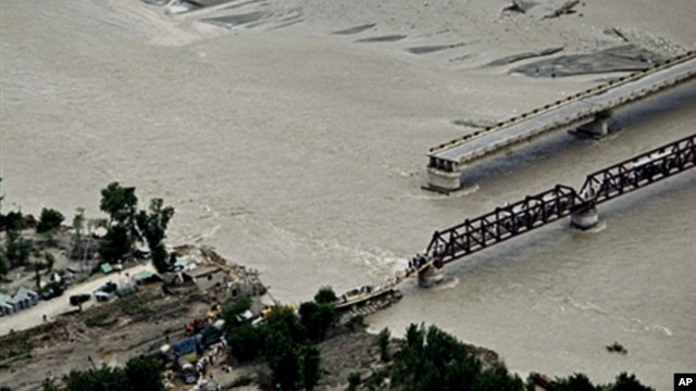 Pakistani flood survivors cross a hastily-repaired bridge next to a main bridge swept away by flood waters in Swat Valley, 10 Aug 2010