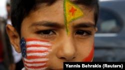 Zarokekî Kurd rûyê xwe bi alên Amerîka, YPG û Kurdistanê reng kiriye