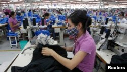 Người lao động làm việc tại nhà máy sản xuất hàng may mặc của Singapore bên ngoài Hà Nội.