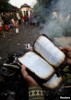 Seorang pengikut Ahmadiyah memperlihatkan Alquran yang terbakar di Ciampea, Jawa Barat, 2 Oktober 2010.
