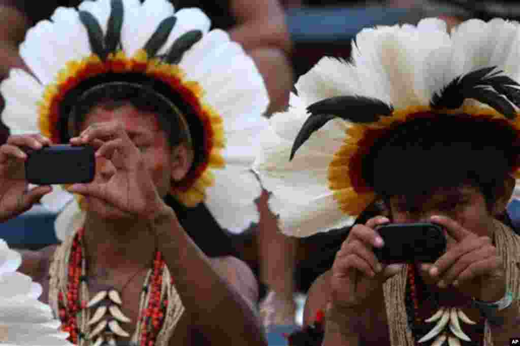 Rikibaktsa Indians take pictures with cell phones during the Indigenous Games on the island of Porto Real in the city of Porto Nacional, Brazil, Monday Nov. 7, 2011. Indigenous people from 38 ethnic groups are participating in the XI Indigenous Games, in