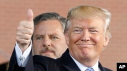 FILE - In this May 13, 2017 file photo, President Donald Trump, right, gives a thumbs up as Liberty University president, Jerry Falwell Jr., left, watches during of commencement ceremonies at the school in Lynchburg, Virginia. For evangelical Christian icons like Jerry Falwell Jr., a Supreme Court that opposes abortion rights is their political holy grail. The Liberty University president is among many religious conservatives who suspect the Supreme Court vacancy President Donald Trump fills in the coming months will ultimately lead to the reversal of the landmark abortion case Roe v. Wade.