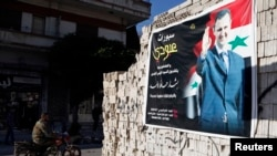 FILE - A man on a motorcycle rides past a poster depicting Syria's President Bashar al-Assad on a wall in the pro-government al-Zahraa neighbourhood in Homs, May 15, 2014.