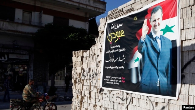 A man on a motorcycle rides past a poster depicting Syria's President Bashar al-Assad on a wall in the pro-government al-Zahraa neighbourhood in Homs May 15, 2014. Despite the carnage and loss of swathes of territory in the north and east to insurgents, S