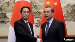 지난달 30일 기시다 후미오 일본 외무상(왼쪽)과 왕이 중국 외교부장이 베이징에서 만나 악수하고 있다.