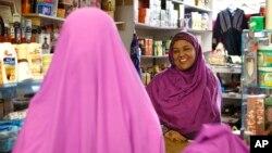 Shukri Abasheikh, owner of Mogadishu Store, speaks with a customer in Lewiston, Maine, Jan. 26, 2016.