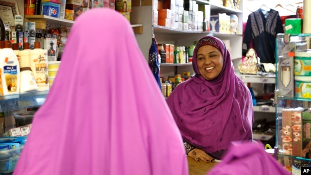 Shukri Abasheikh, owner of Mogadishu Store, speaks with a customer in Lewiston, Maine, Jan. 26, 2016.