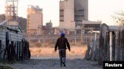 A township resident walks past Lonmin's platinum mine in Marikana, South Africa, June 13, 2014.
