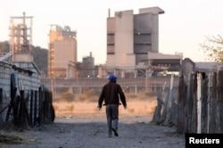 FILE - A township resident walks past Lonmin's Marikana platinum mine, June 13, 2014.