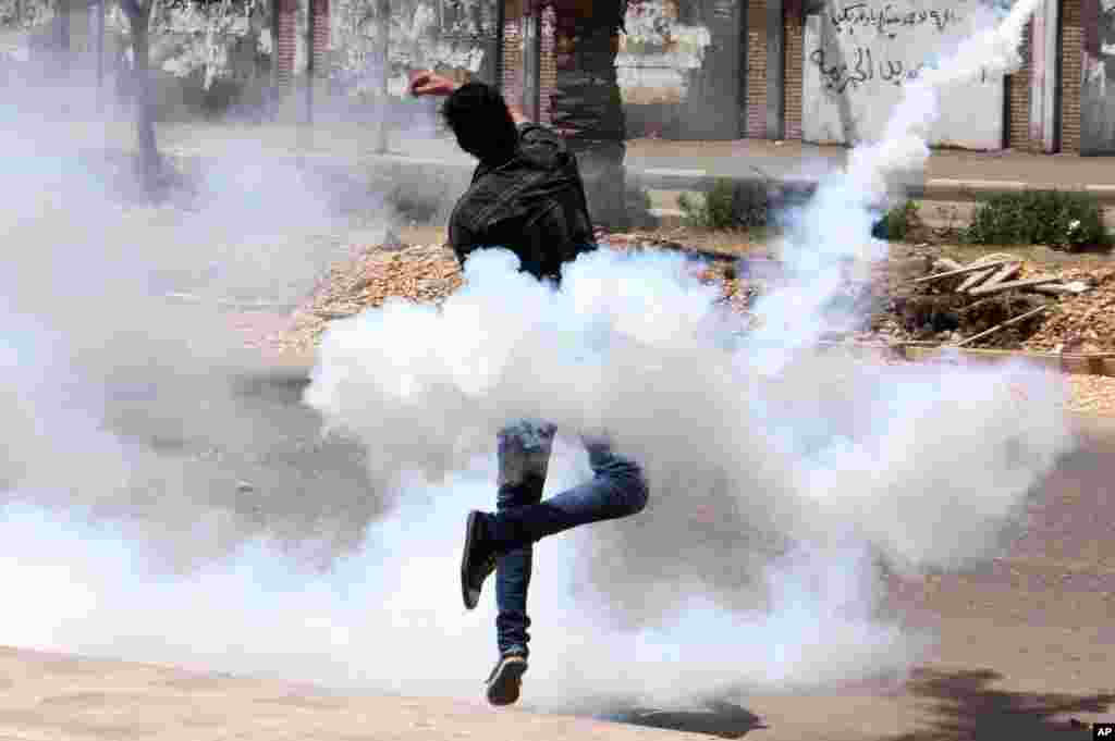 A bystander throws a tear gas canister that came back from the al-Azhar University campus after the canister was originally shot by the Egyptian security forces towards protesters at the school in Cairo.