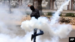 Seorang laki-laki melempar tabung gas air mata kembali ke arah Univ. al-Azhar sesudah tabung itu sebelumnya ditembakkan oleh petugas keamanan Mesir ke arah protester di universitas itu, di Kairo (2/5/2014).