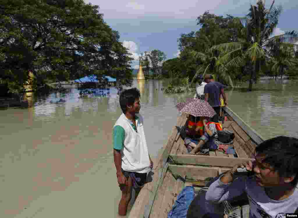 A boat man (left) stands on the roof of a flooded home next to a media boat in Kalay township, a village in the Sagaing region, northwestern Myanmar, Aug. 2, 2015.
