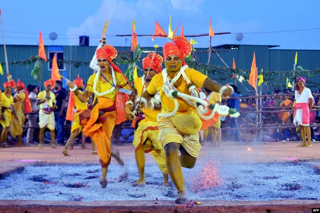 """Индуистские преданные бегут через красные горячие угли как часть ежегодного ритуала ходьбы огня во время фестиваля """"Draupadi Amman"""" в Бангалоре, Индия."""