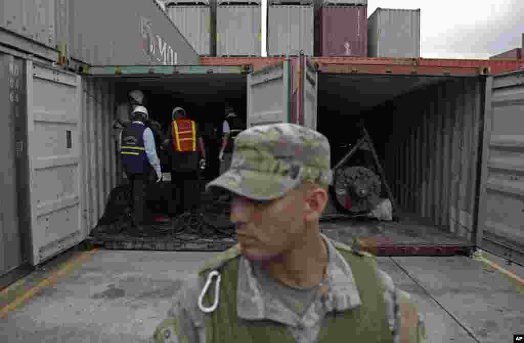A police officer stands guard as investigation officers look inside a container holding military equipment aboard the North Korean-flagged freighter, Chong Chon Gang, at the Manzanillo International container terminal, Colon City, Panama.