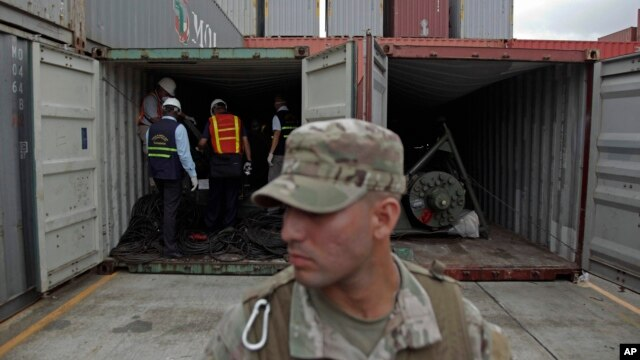 FILE - A police officer stands guard as investigation officers look inside a container holding military equipment aboard the North Korean-flagged freighter Chong Chon Gang at the international container terminal at Colon City, Panama.