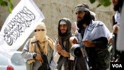 افغان طالبان ایک پرچم اٹھائے ہوئے ہیں۔ فائل فوٹو