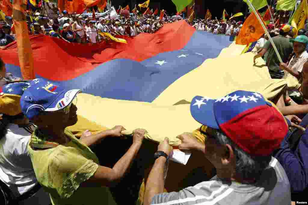 La bandera venezolana es ondeada entre los manifestantes opositores.
