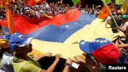 Pendukung oposisi kibarkan bendera national dal am demo menentang pemerintah Presiden Venezuela Nicolas Maduro