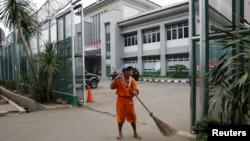 A worker sweeps at the gate of Cipinang prison in Jakarta, Jan. 17, 2016. Islamist cleric Aman Abdurrahman, who has led an Islamic State-affiliated militant network from the prison, was released early for Indonesia's Independence Day Thursday. He is back in jail and being questioned about his role in a January 2016 attack.