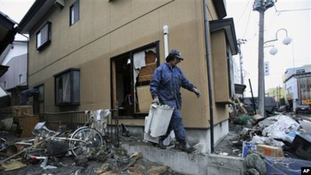 A resident cleans up tsunami debris in his destroyed house Tuesday, March 15, 2011, in Soma city, Fukushima prefecture, Japan.