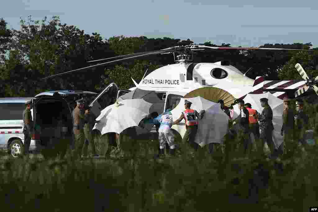 Police and military personnel use umbrellas to cover around a stretcher near a helicopter and an ambulance at a military airport in Chiang Rai as rescue operations continue for those still trapped inside the cave in Khun Nam Nang Non Forest Park in the Mae Sai district, Thailand.