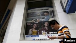FILE - A man checking his smartphone walks past a bank advertisement in Hong Kong, China, Nov. 30, 2015. Recent research indicates that outlay on digital advertising in China has surpassed the amount spent on traditional ads.