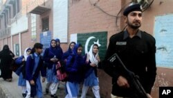 A Pakistani police officer stands guard as children make their way to school in Lahore, Pakistan, Monday. Pakistani authorities closed schools last week, in the country's largest province, Punjab, following warnings of possible militant attacks. The U.S. will give Pakistan over $800 million in foreign aid in 2016. (AP Photo/K.M. Chaudary)