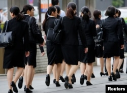 Female office workers wearing high heels, clothes and bags of the same color make their way at a business district in Tokyo, Japan, June 4, 2019. (REUTERS/Kim Kyung-Hoon)