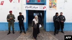 Tunisian security officers stand guard outside at a polling station in the center of Tunis on Nov. 23, 2014, during Tunisia's first presidential election since the 2011 revolution.