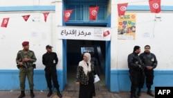 2014年11月23日,突尼斯安保人员守卫在突尼斯市中心一个投票站外面。这是2011年突尼斯革命以来这个国家举行的首次总统选举。