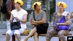 중국 상하이 등에서 기록적인 폭염이 계속되는 가운데, 31일 더위를 식히기 위헤 물수건을 머리에 얹은 주민들.