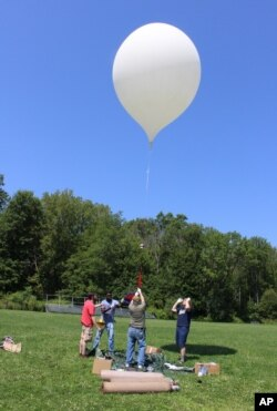 An 8-foot camera-carrying balloon rises into the sky during a test launch at the University of Hartford in West Hartford, Conn., Aug. 9, 2017. A team from the University of Bridgeport and the University of Hartford conducted the test as part a project that will send cameras into the stratosphere to photograph this month's solar eclipse.