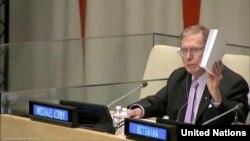 마이클 커비 전 위원장이 22일 유엔에서 열린 북한인권토론회에서 북한인권상황을 비판하며 COI 보고서를 들어 올리고 있다.